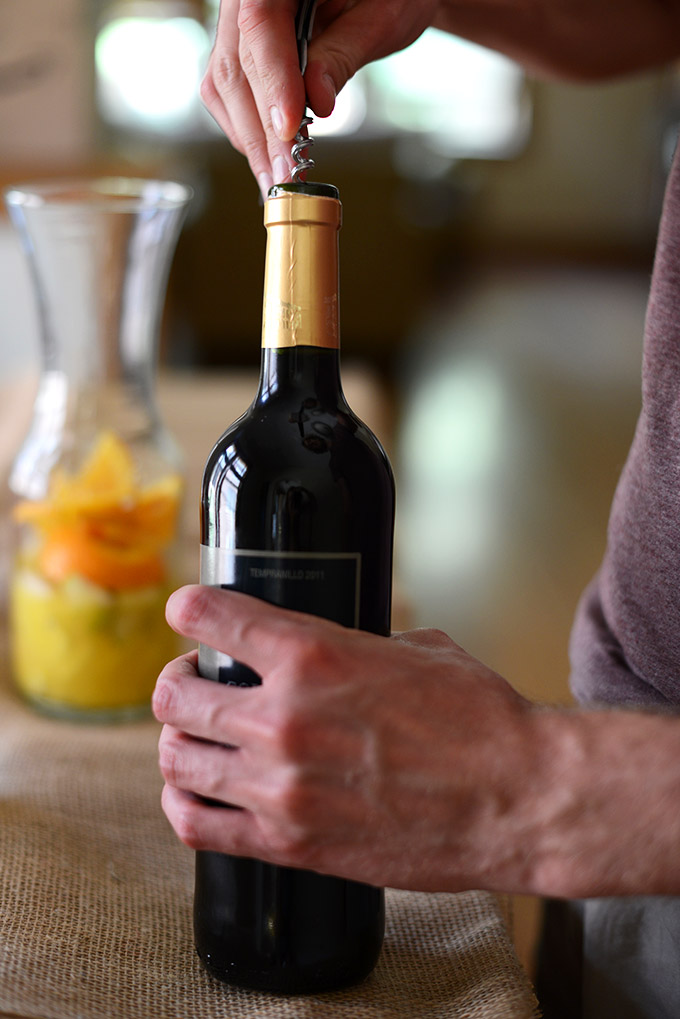 Using a corkscrew to open a bottle of wine for homemade Spanish Sangria