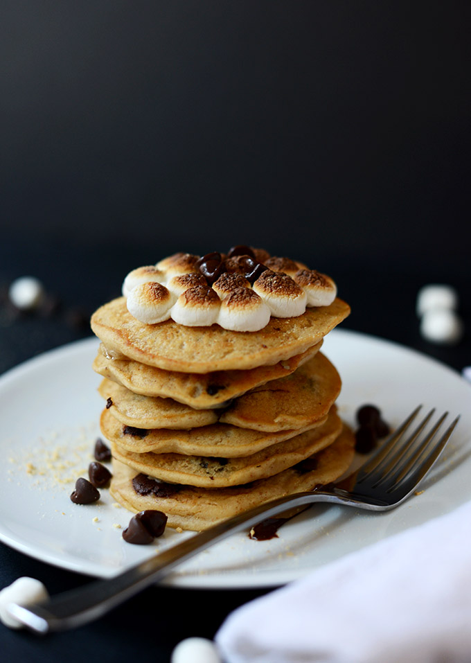 Stack of vegan pancakes with toasted marshmallows and melted chocolate on top