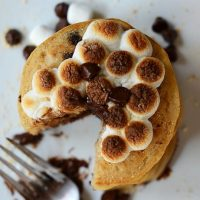 Top down shot of a stack of Vegan Smores Pancakes topped with toasted marshmallows and chocolate chips
