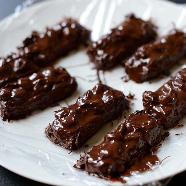 Plate of homemade Vegan Snickers Bars on plastic wrap