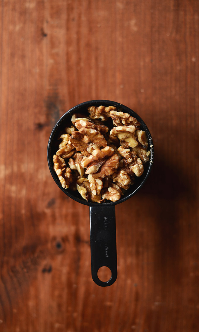 Measuring cup filled with walnuts for making Vegan Snickers Bars