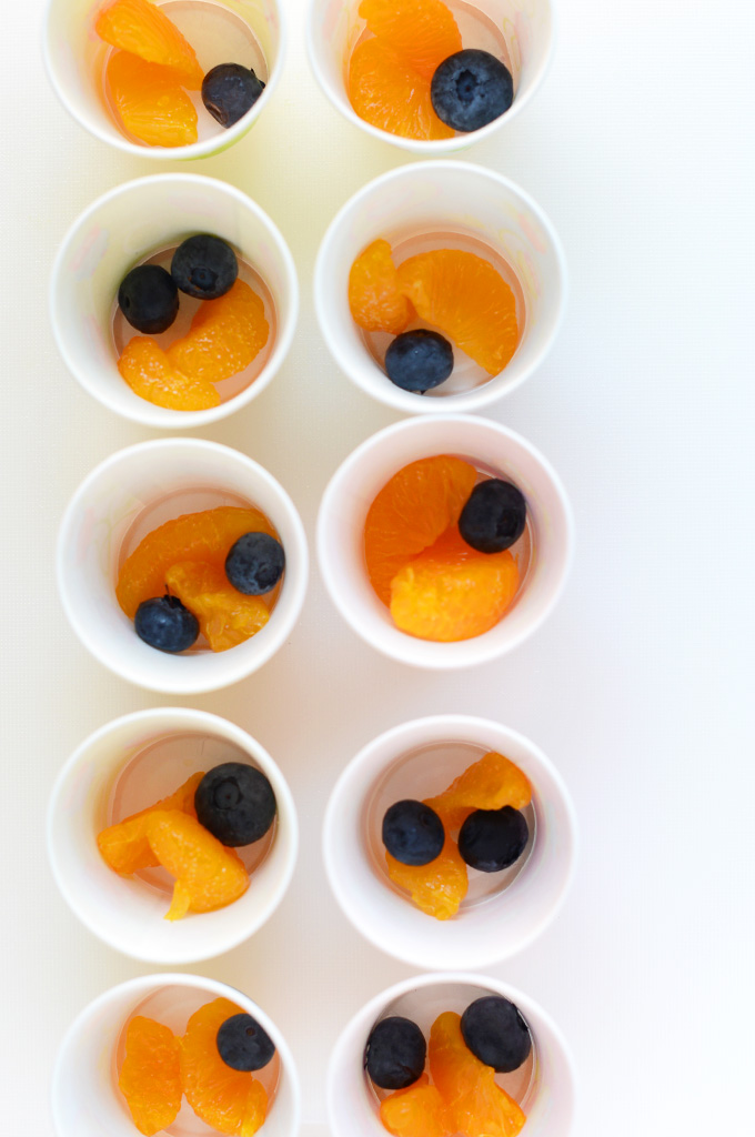 Making homemade fruit popsicles in small cups