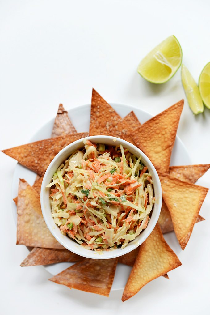 Bowl of Creamy Thai Slaw surrounded by Baked Wonton Chips and limes