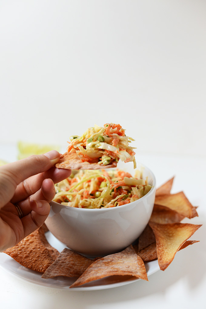 Using a chip to scoop up a bite of Creamy Thai Slaw