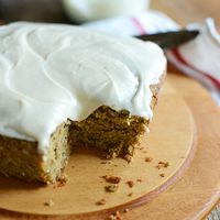 Frosted Gluten-Free Zucchini Cake on a cutting board with a slice removed