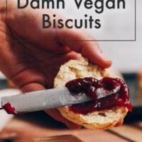 Spreading jam onto a vegan biscuit