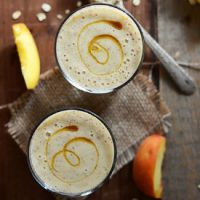 Top down shot of two glasses filled with our Peach Oat Smoothie recipe