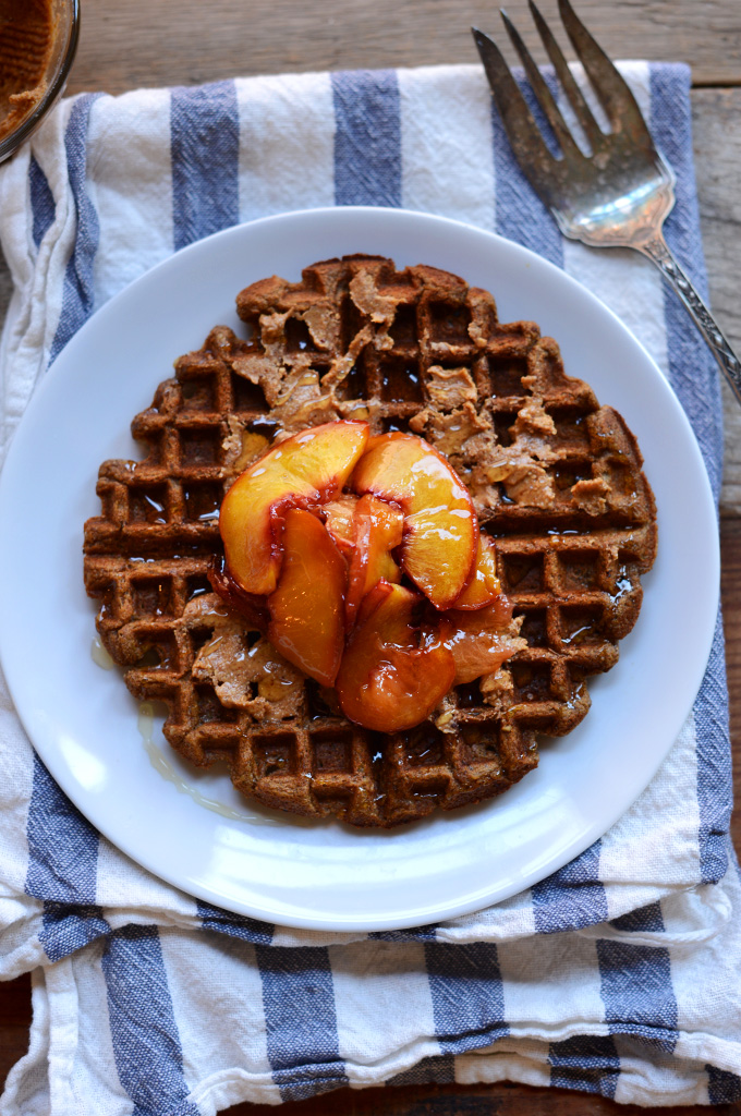 Whole Grain Vegan Waffle topped with maple syrup and roasted peaches