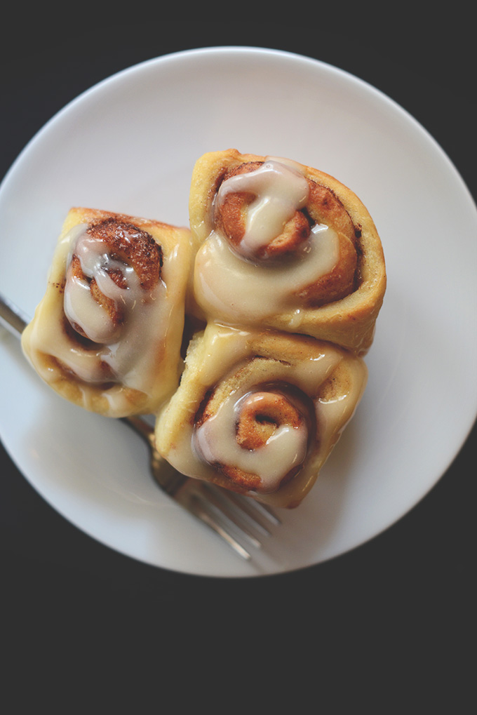 Plate of three Vegan Cinnamon Rolls topped with icing