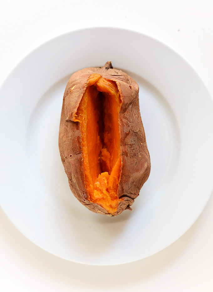 Plate with a freshly baked and sliced open sweet potato