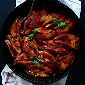 Spoon in a skillet of Dairy-Free Stuffed Shells topped with fresh basil