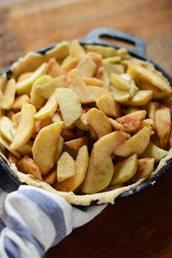 Cast-iron skillet filled with crust and apples for homemade apple pie