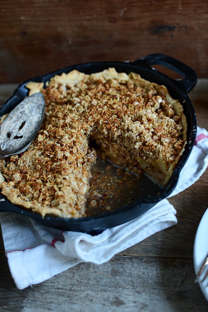 Skillet of vegan Deep Dish Apple Crumble Pie with a slice removed