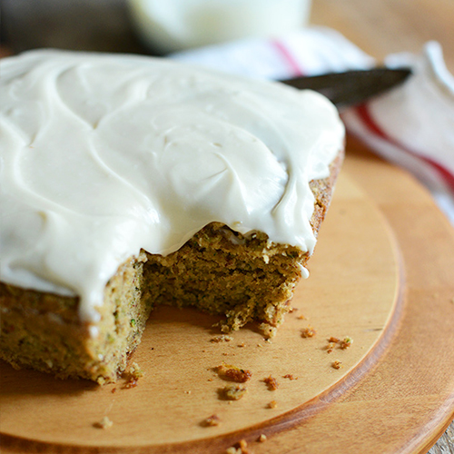 Cutting board with a loaf of Gluten-Free Zucchini Cake topped with frosting