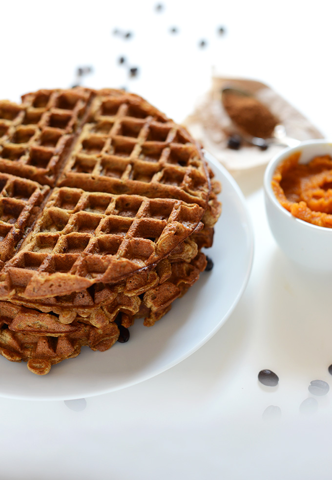 Stack of Pumpkin Spice Waffles alongside a bowl of puree pumpkin