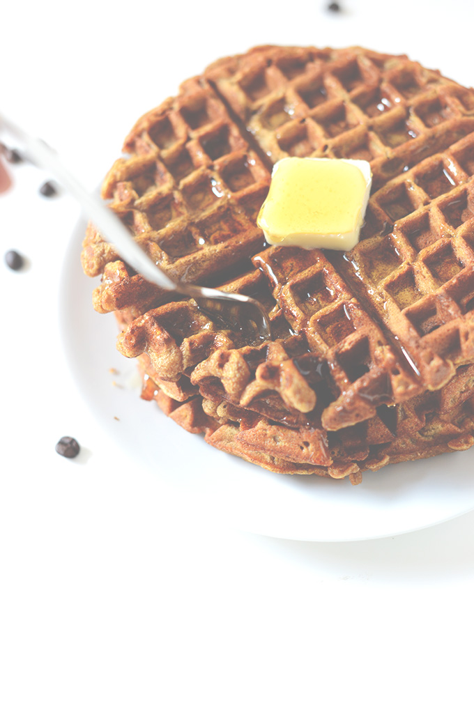 Using a fork to grab a bite of delicious Pumpkin Spice Waffles for breakfast