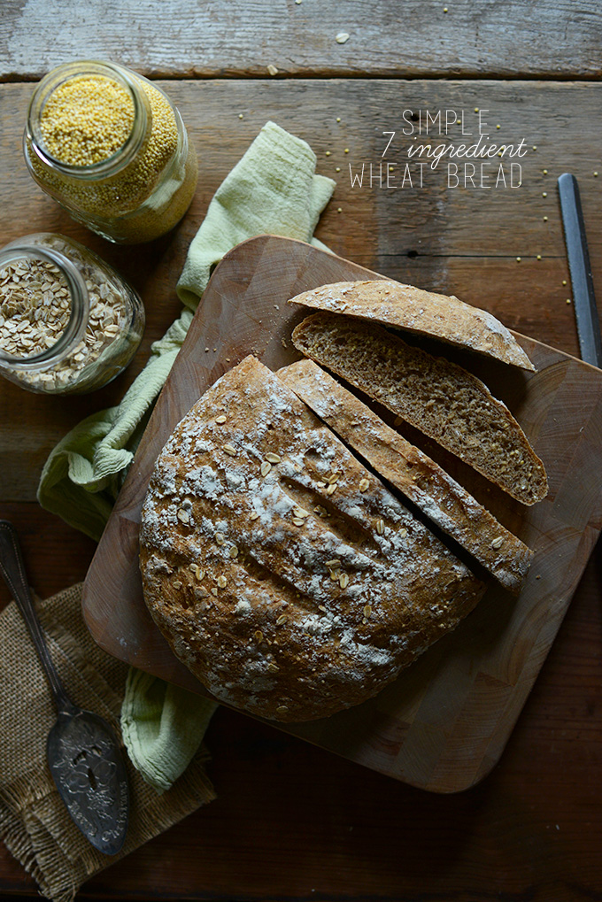 Partially sliced loaf of whole grain Wheat Bread with jars of oats and millet
