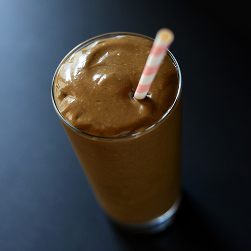 Tall glass of our Triple Chocolate Avocado Shake recipe with a pink and white straw