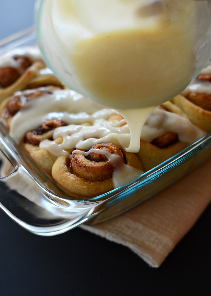 Drizzling icing over a batch of Vegan Cinnamon Rolls