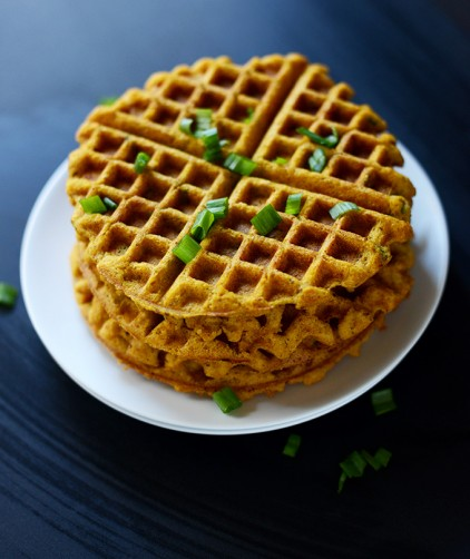 Stack of Crispy Savory Pumpkin Cornbread Waffles topped with green onion