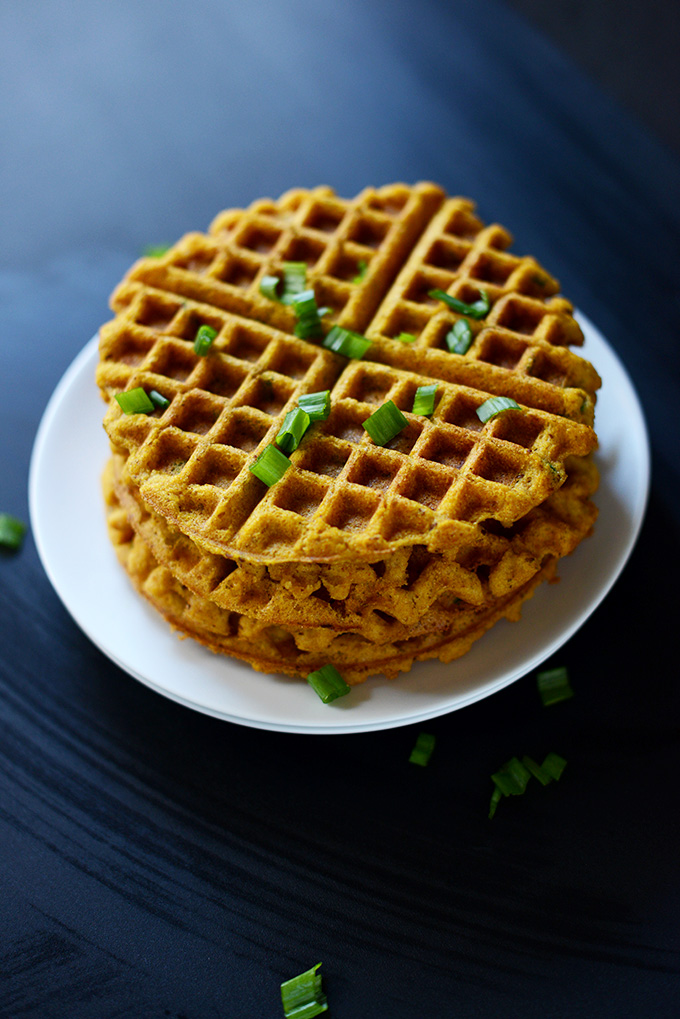 Stack of vegan Savory Pumpkin Cornbread Waffles topped with green onions