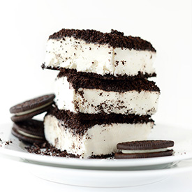 Slices of Vegan Dirt Cake on a small plate with three oreo cookies