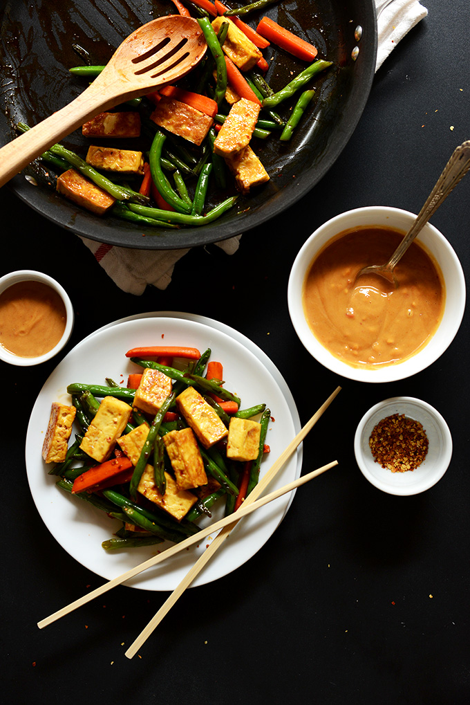 Plate and skillet of Tofu Stir Fry with bowls of peanut sauce and red chili flakes