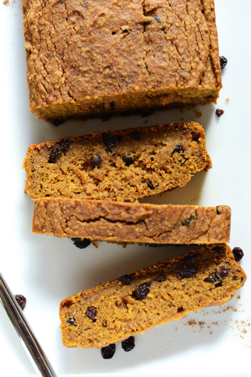 Cascading partially sliced loaf of Easy Vegan Pumpkin Bread with dried currants