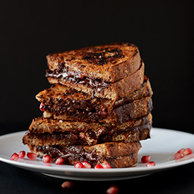 Stack of Grilled Almond Butter, Dark, Chocolate, & Pomegranate sandwiches on a plate