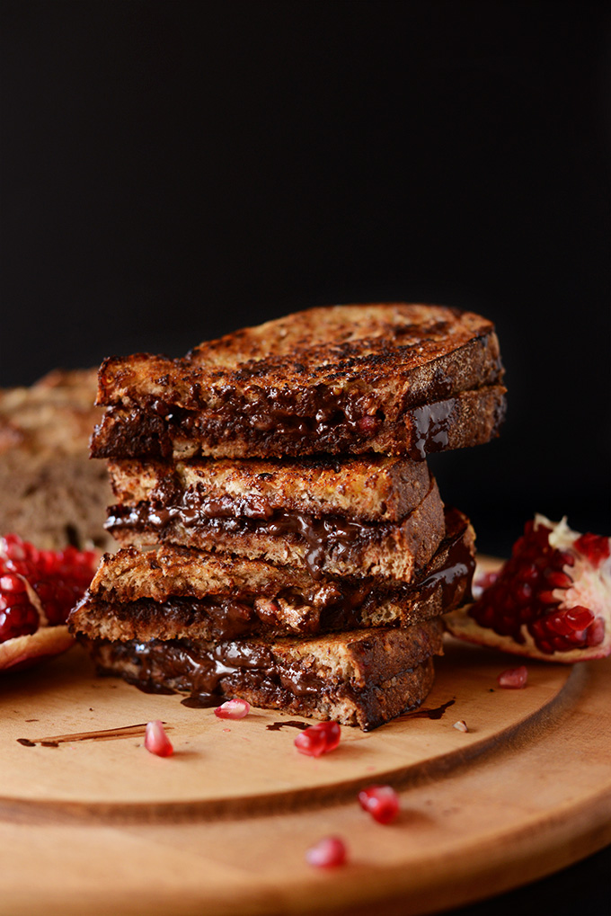 Grilled Almond Butter, Dark Chocolate, Pomegranate Sandwiches piled high on a cutting board