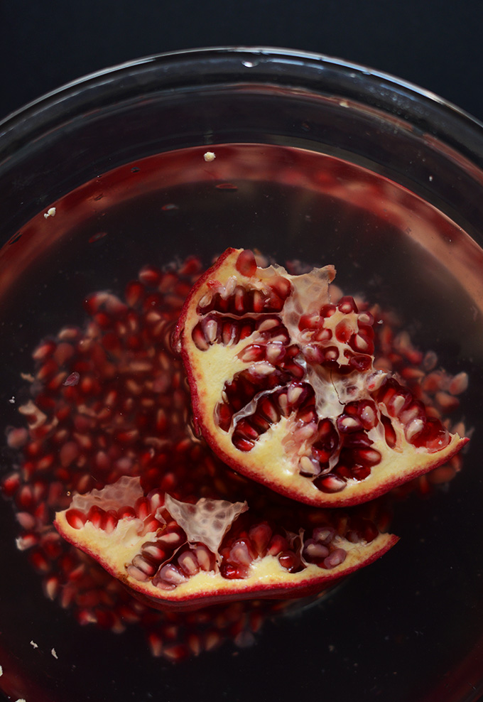 Bowl of pomegranate seeds and fresh pomegranate ready to have its seeds removed