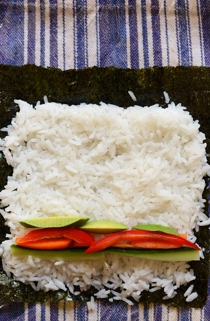 Nori sheet topped with rice and vegetables for making homemade sushi