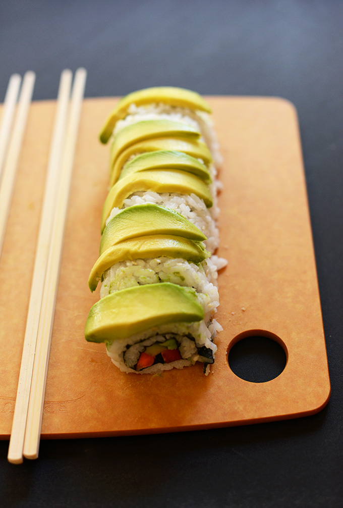 Inside Out Avocado Sushi Roll on a on a cutting board with chopsticks