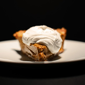 Plate with a slice of No Bake Pumpkin Pie topped with coconut whipped cream