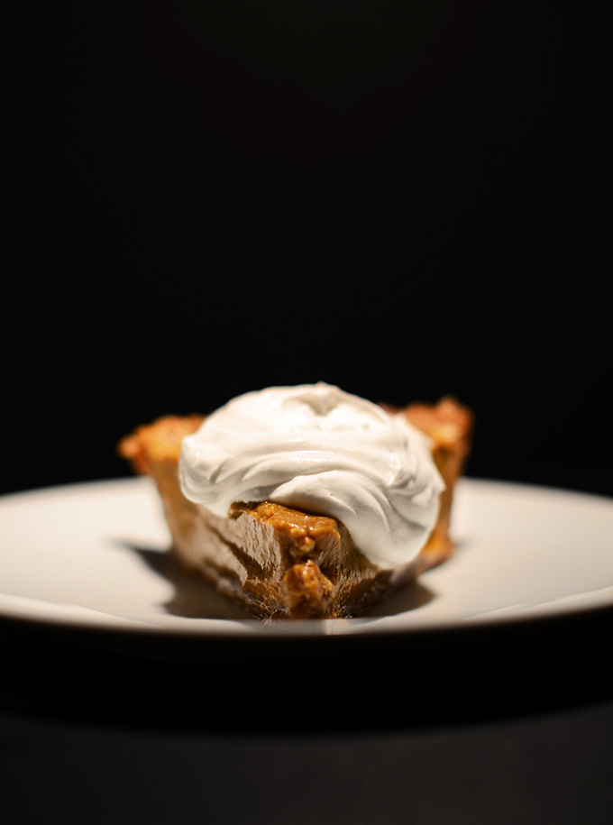 Plate with a slice of No-Bake Pumpkin Pie topped with a big dollop of coconut whipped cream