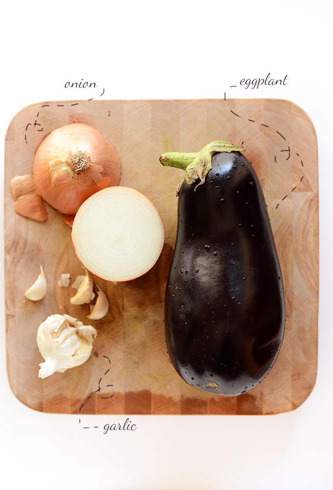 Cutting board with onions, garlic, and eggplant for making Persian Eggplant Dip