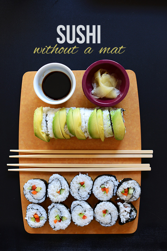 Wood board with sushi rolls, pickled sushi ginger, and soy sauce for dipping
