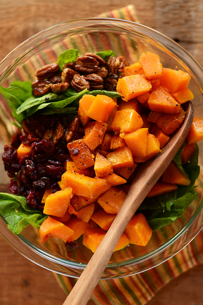 Big bowl of Roasted Butternut Squash Salad with dried cranberries and caramelized pecans
