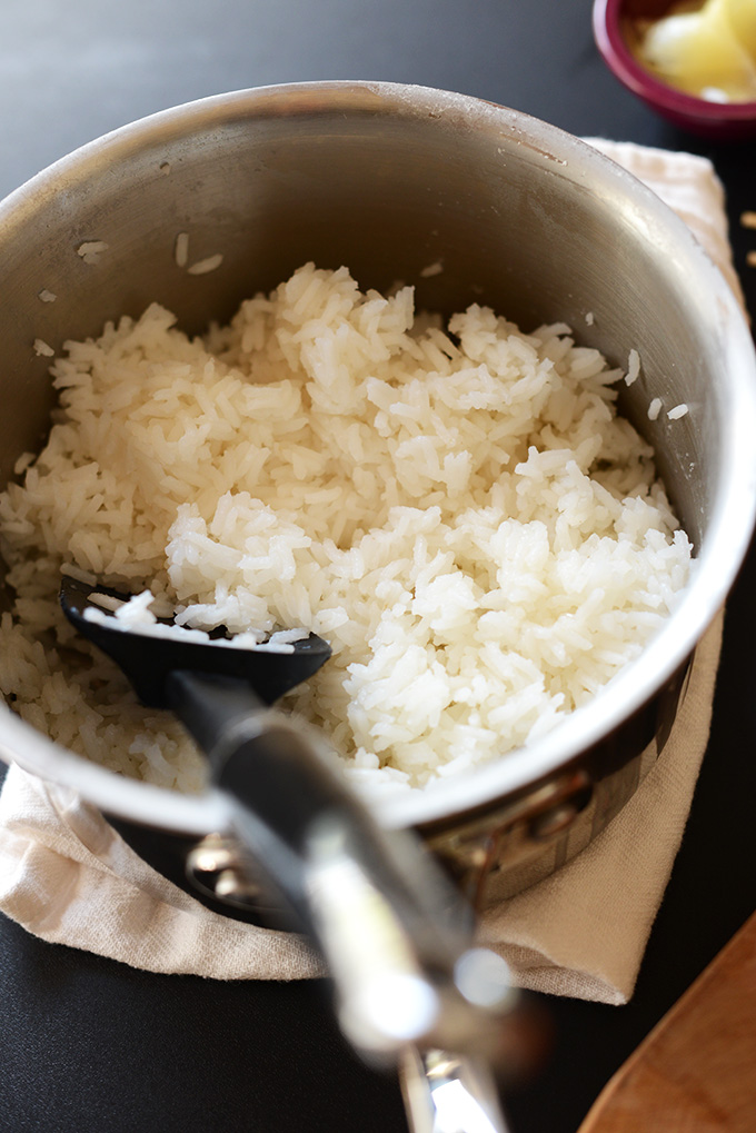 backlit view of white rice cooked in a saucepan with a spatula scooping some rice.