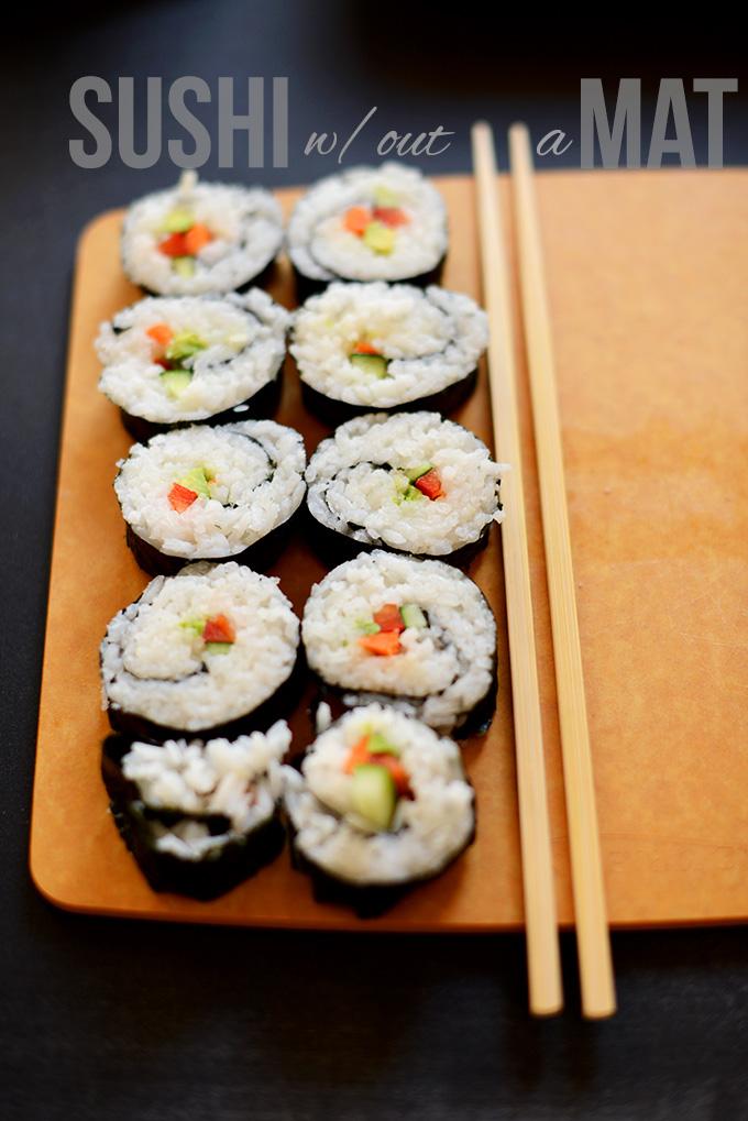 Sliced Vegan Sushi Rolls on a cutting board with chopsticks