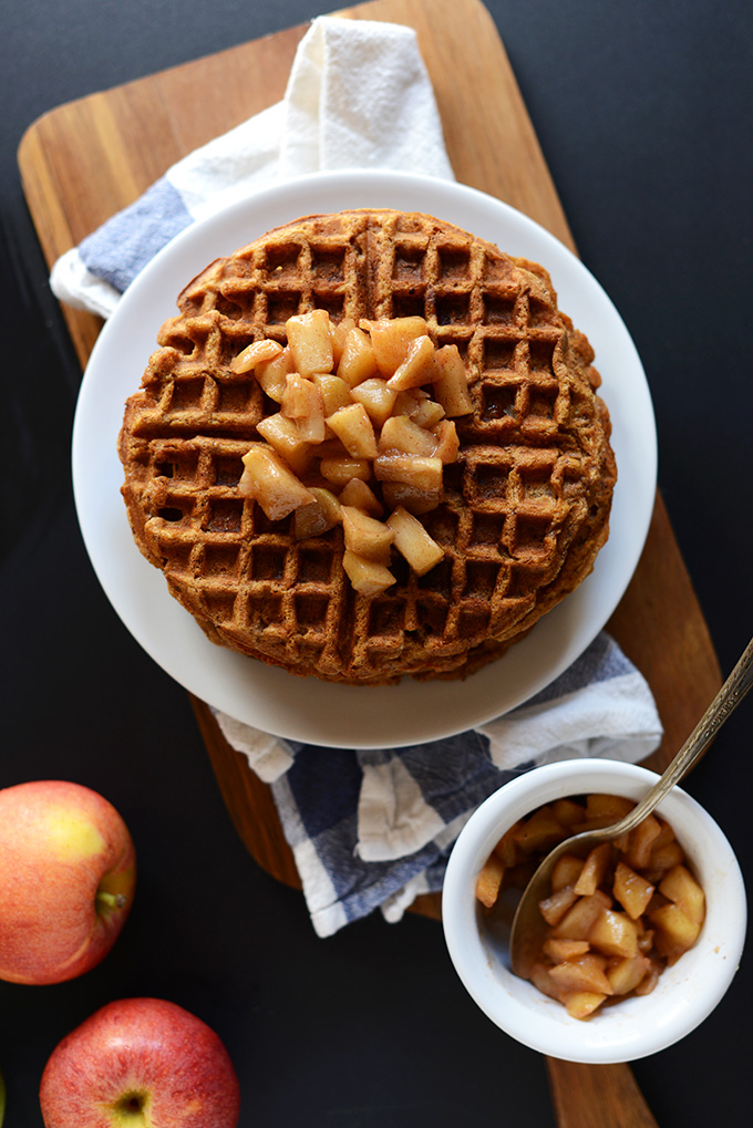 Plate of Vegan Apple Waffles and small bowl of extra cinnamon apples