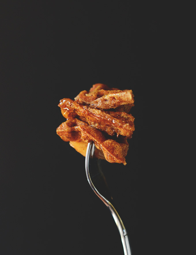 Holding up a fork with a big bite of Vegan Cinnamon Apple Waffles