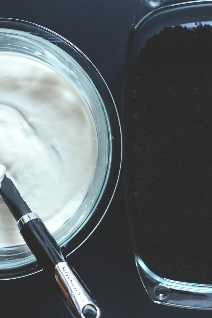 Mixing bowl of filling and baking dish of cookie base for Vegan Kansas Dirt Cake