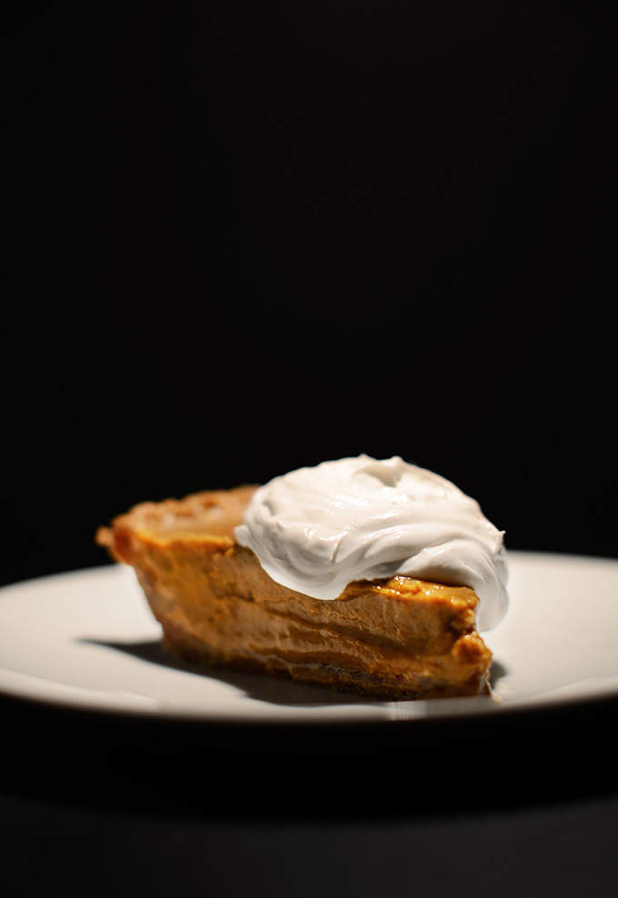 Slice of Vegan No-Bake Pumpkin Pudding Pie with coconut whipped cream