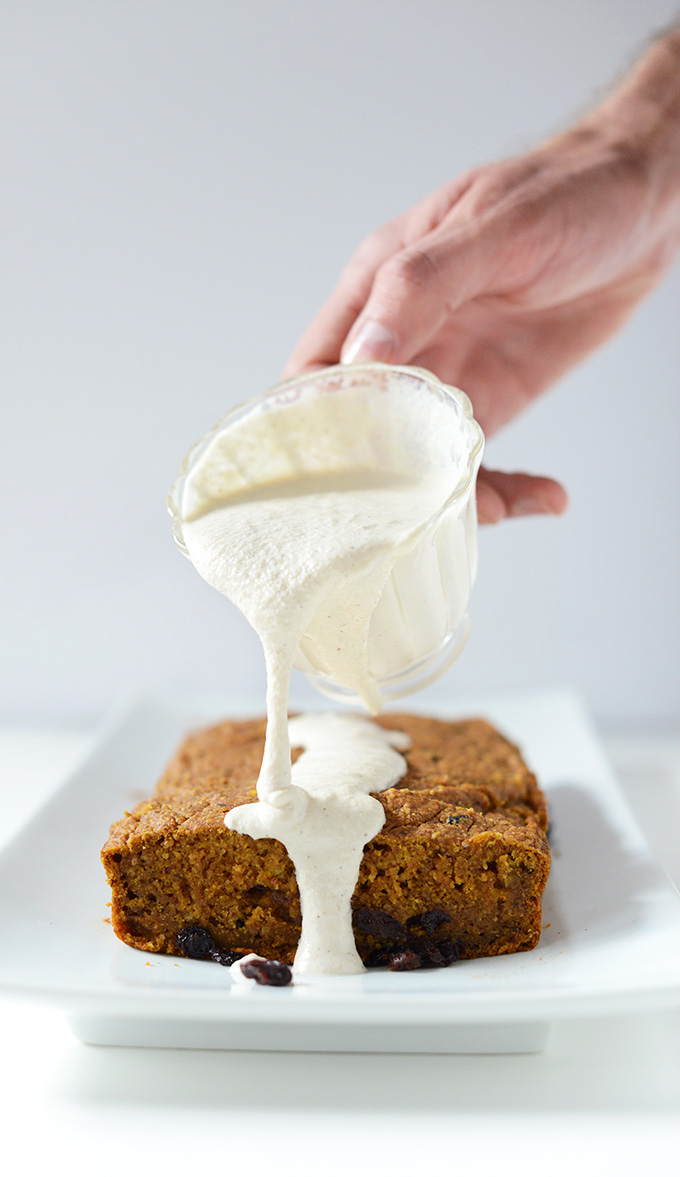 Drizzling Maple Cashew Frosting onto a loaf of Vegan Pumpkin Bread