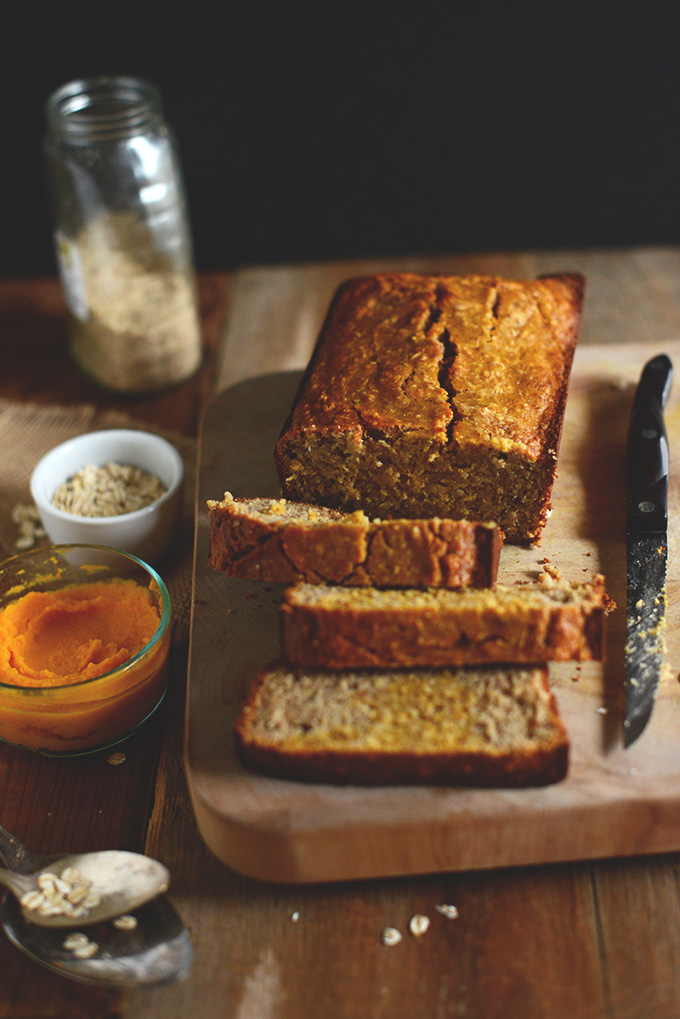 Cascading partially sliced loaf of Gluten-Free Banana Bread with bowls of oats and squash