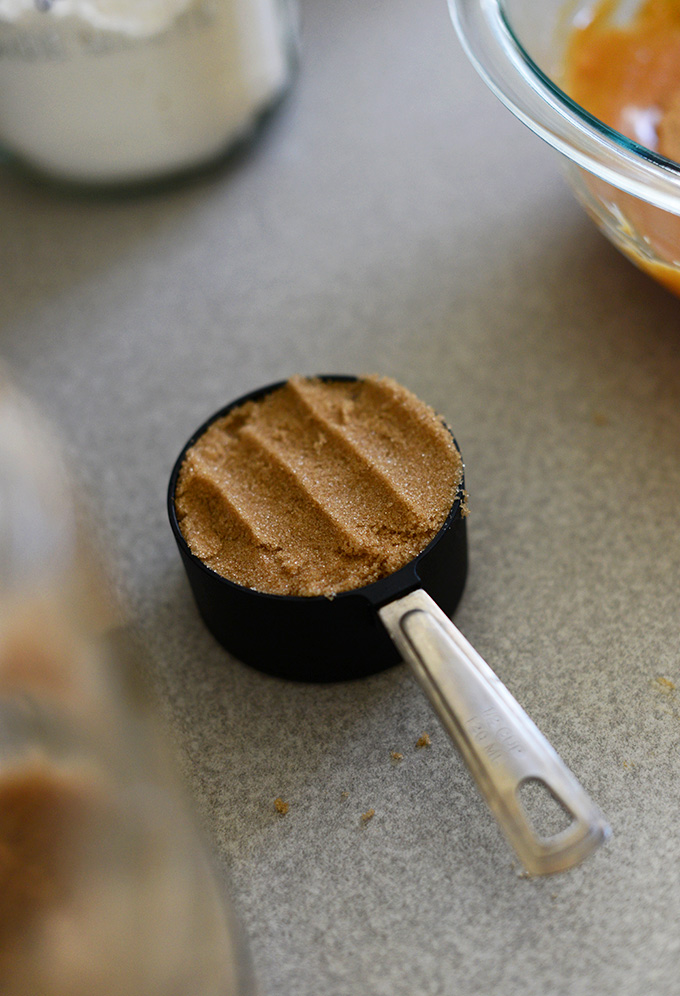 Measuring cup filled with brown sugar for making Vegan Peanut Butter Cookies