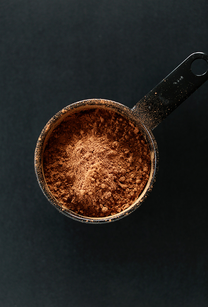 Measuring cup of cocoa powder for making gluten-free vegan brownies