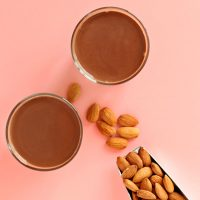 Scoop of almonds and two glasses of our DIY Chocolate Almond Milk recipe