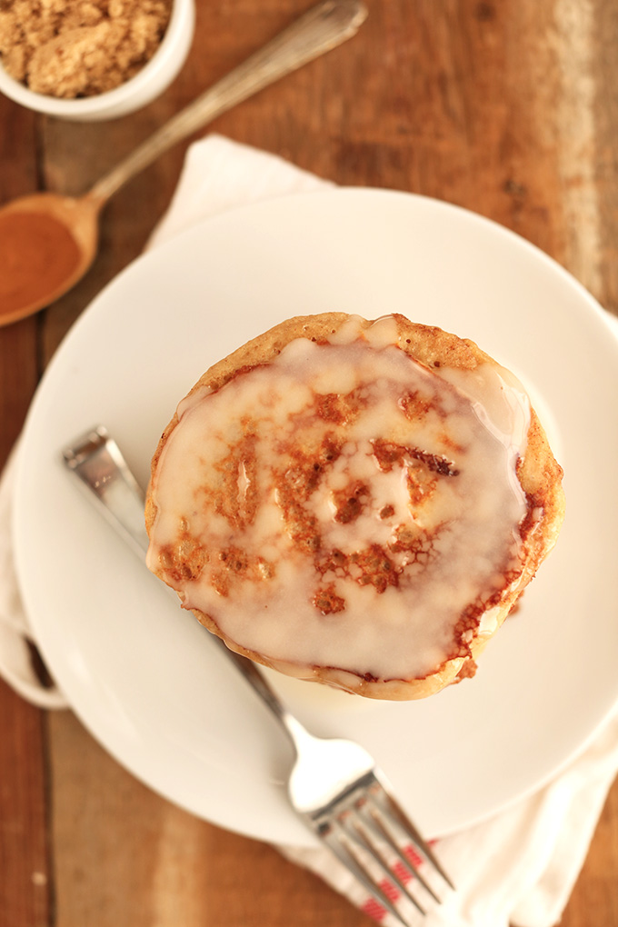Plate with a batch of Easy Cinnamon Roll Pancakes topped with icing